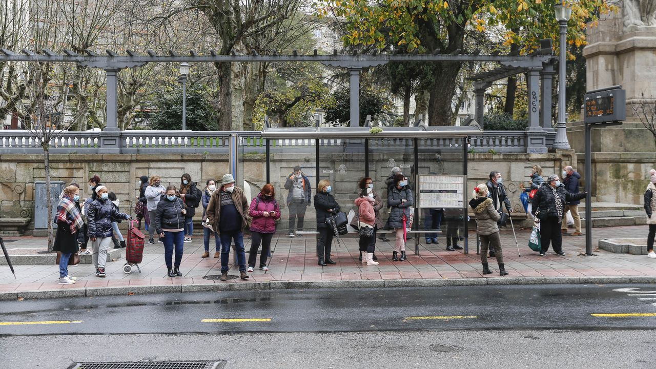 Usuarios esperando por un autobús en la parada del Parque de San Lázaro