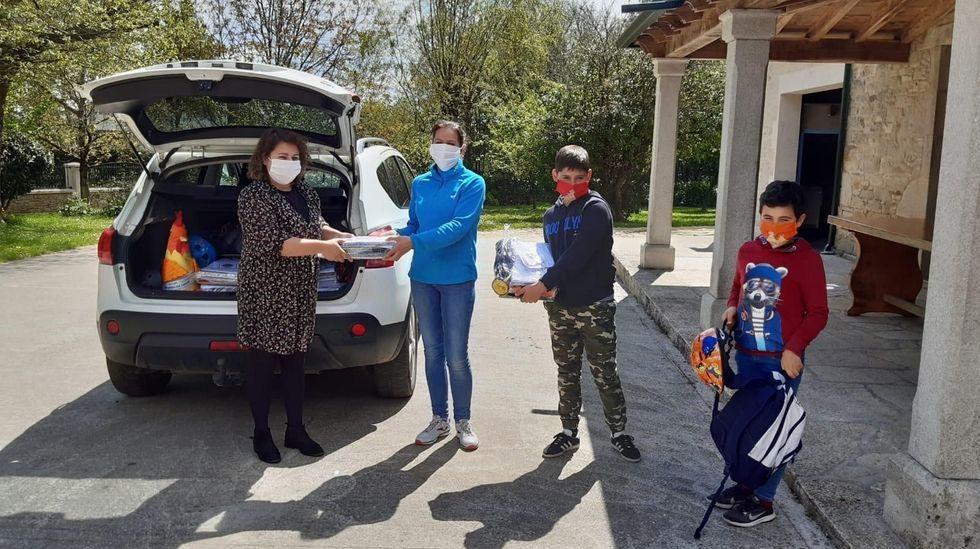 En los lugares pequeños el reparto se está haciendo. En la imagen, Irene Díaz, a la izquierda, directora del CEIP Monseivane (de Lanzós, en Vilalba) entrega material escolar a una familia