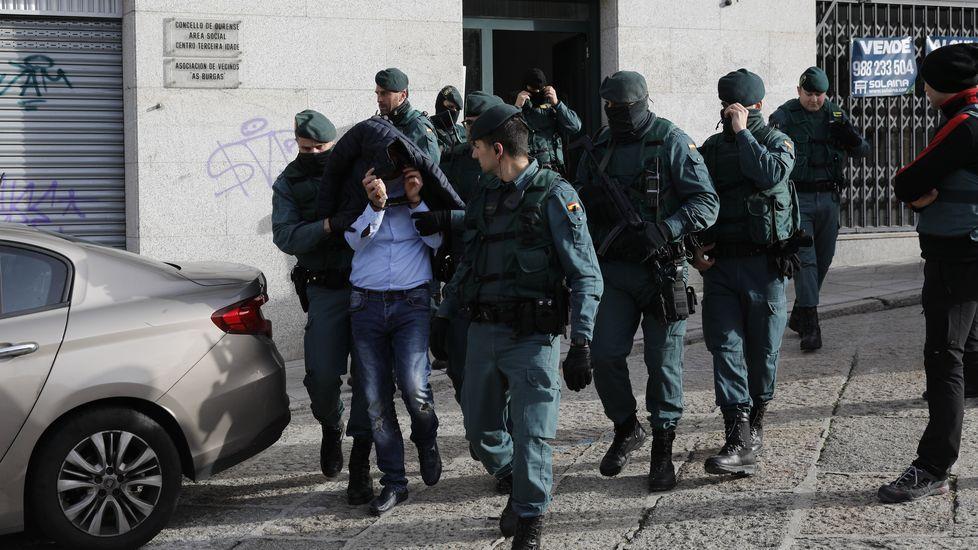 Uno de los detenidos en Ourense, rodeado de guardias civiles a la salida tras el registro de una casa en la calle Burgas