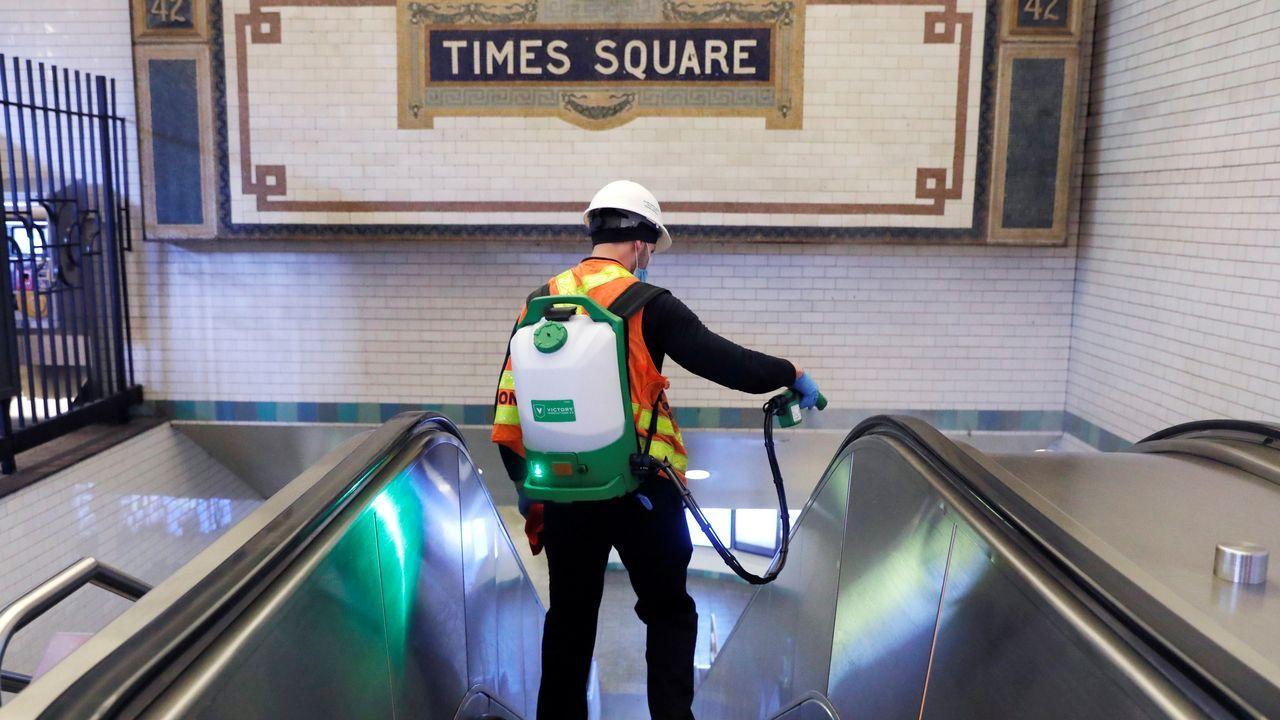 Un empleado desinfecta la estación de Times Square del metro de Nueva York durante la noche