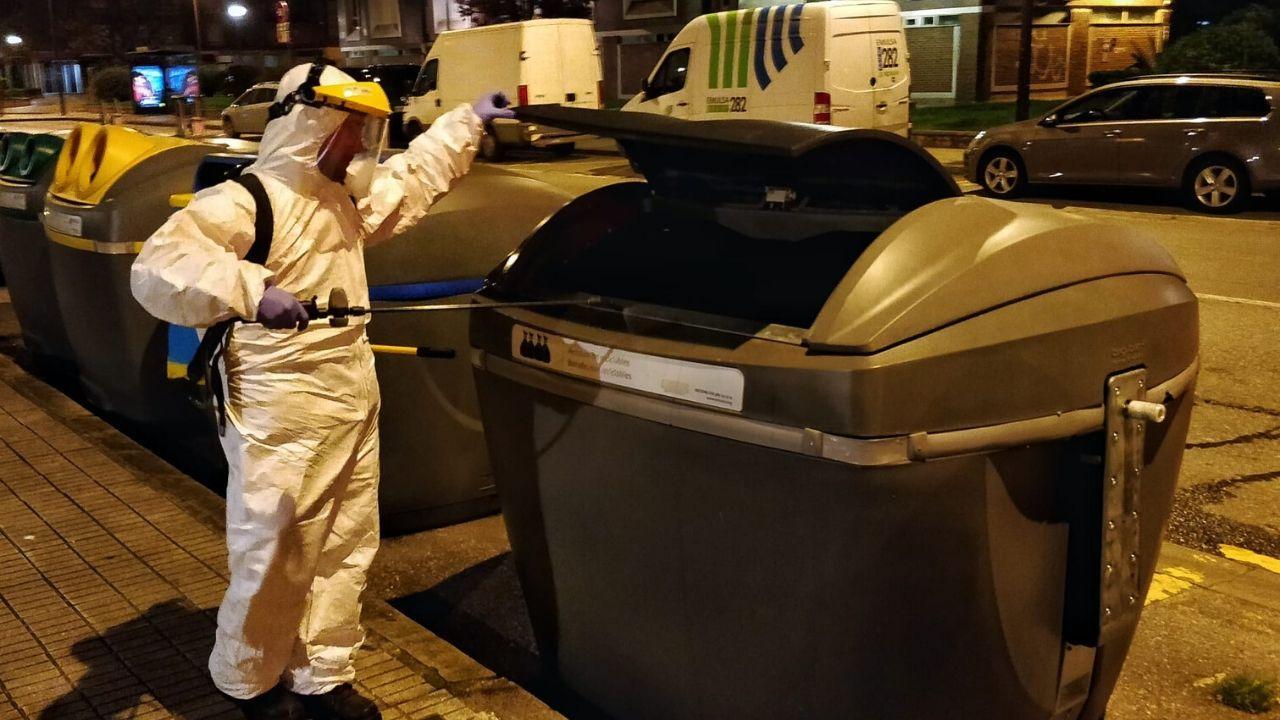 Un operario de Emulsa desinfecta un contenedor en una calle de Gijón