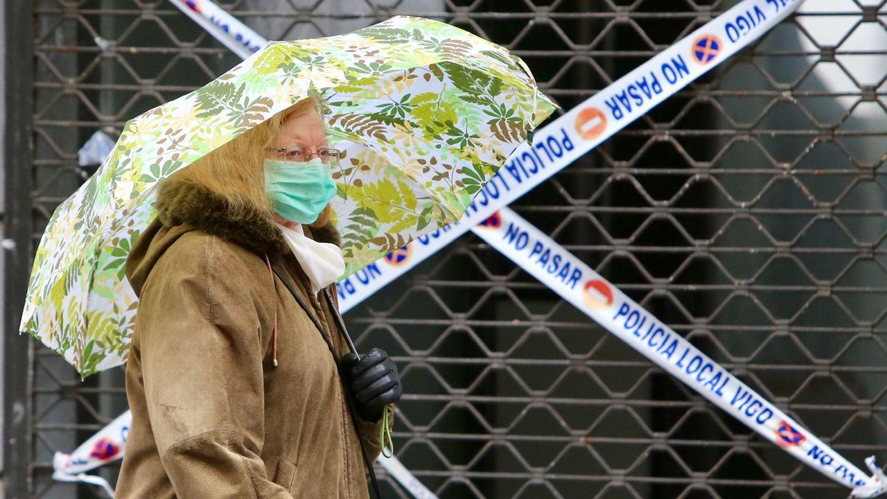 combo galegos 1.Un hombre en una protesta en Berlín contra las restricciones, con una braga a modo de mascarilla y un cartel sobre la protección.