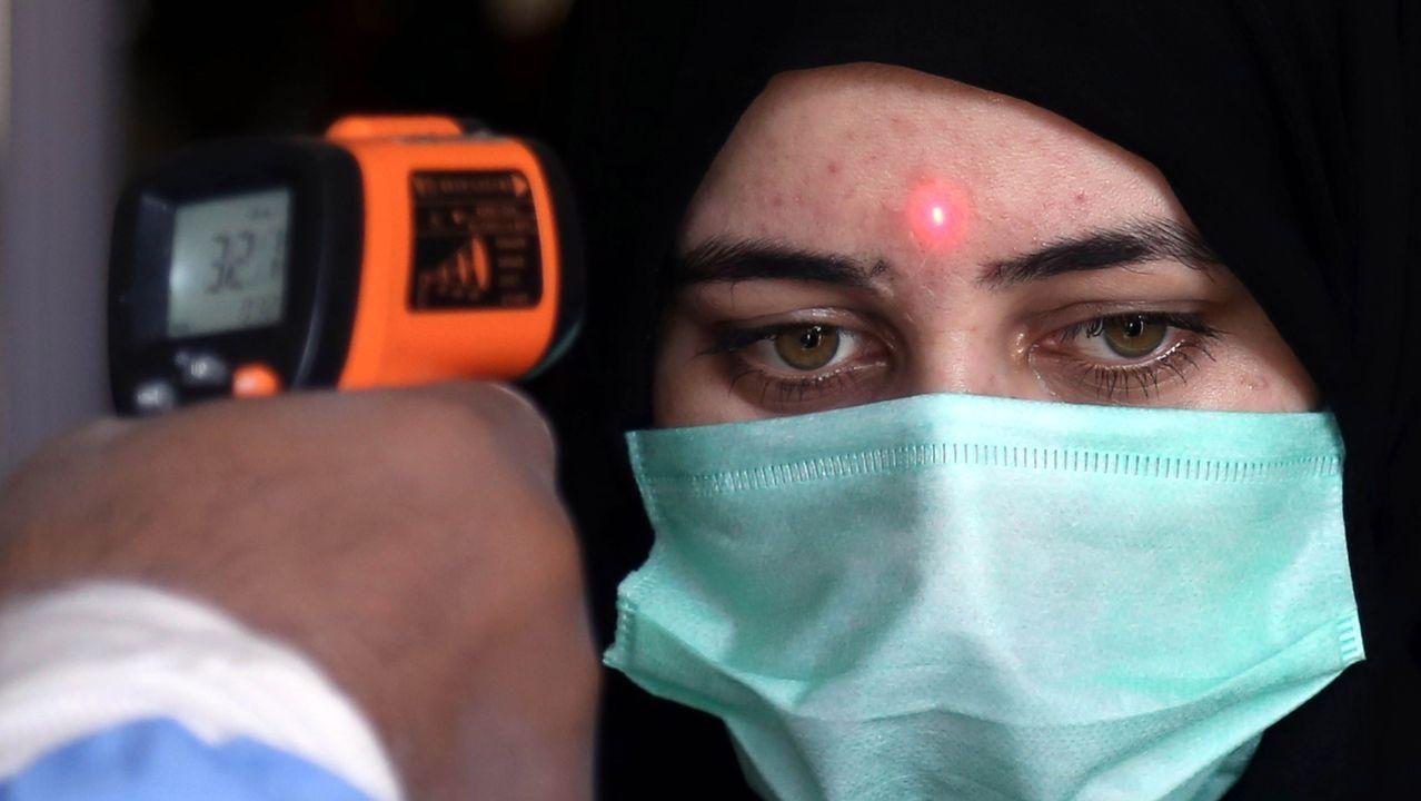 Un trabajador de una estación de tren medía ayer la temperatura de una pasajera en Karachi (Pakistán)