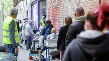 Vecinos realizan una cola para recoger bolsas de la Asociación de Vecinos Parque Aluche (Madrid) donde los voluntarios han entregado alimentos y productos donados en su sede ubicada en la calle Quero nº 69 a aquellas personas que lo necesitan