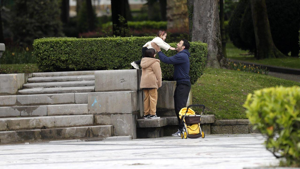 Un paciente de 80 años recibe el alta de la UCI del HUCA.Un hombre juega con sus hijas en un parque del centro de Oviedo