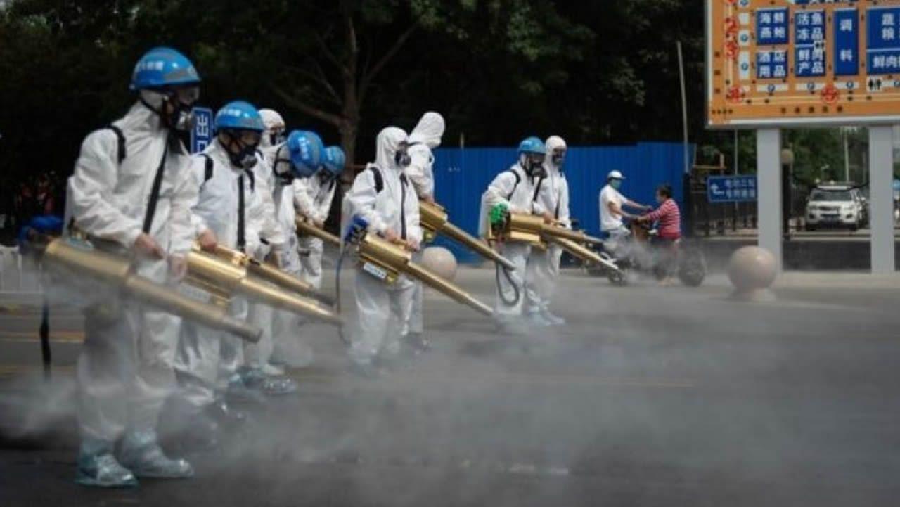 Miembros del equipo de limpieza de Pekín desinfectan un mercado mayorista de la capital china