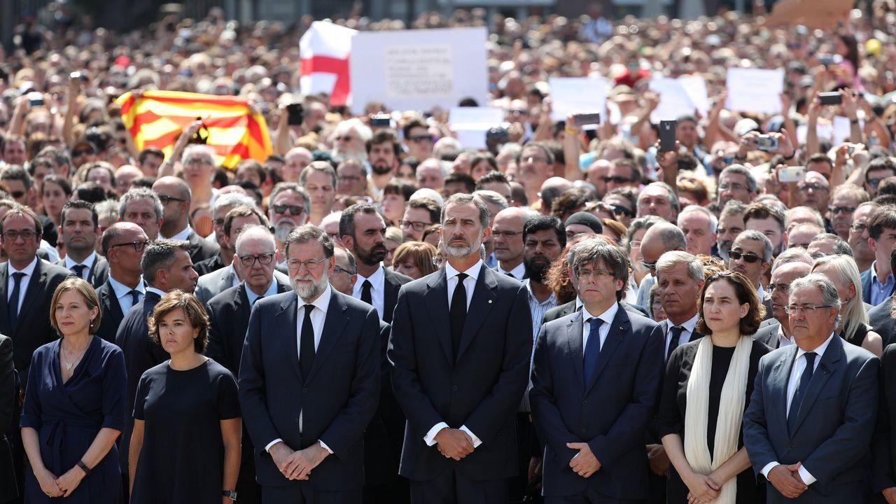 El rey Felipe, la vicepresidenta del Gobierno, Soraya Sáenz de Santamaría, el presidente Mariano Rajoy, el presidente de la Generalitat, Carles Puigdemont y la alcaldesa de la ciudad, Ada Colau, guardan en la Plaza de Cataluña un minuto de silencio