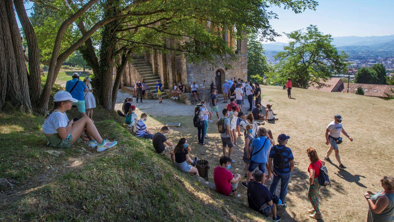 Grupos de turistas se protegen del calor en el exterior del monumento prerrománico de Santa María del Naranco