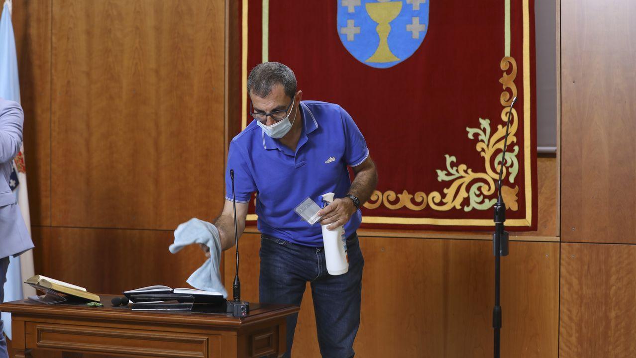 Un trabajador del Parlamento desinfecta el atril desde el que hablará el presidente de la Xunta para tomar posesión