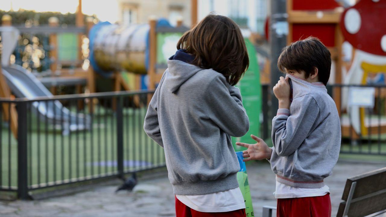 Galicia apura el primer día de paseos.Dos niños se tapan la boca con sudaderas ante un parque cerrado en la Plaza de Galicia de Santiago