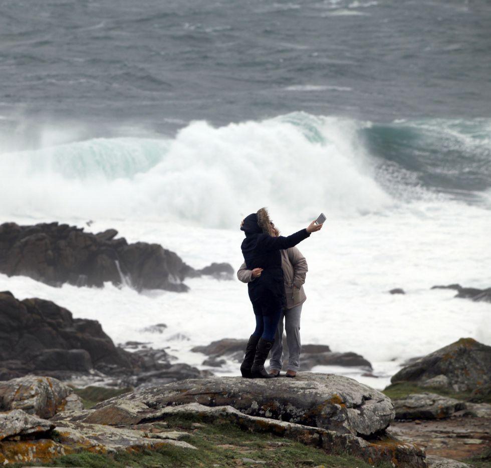 Dos personas se hacen un «selfie» en las rocas de Corrubedo.