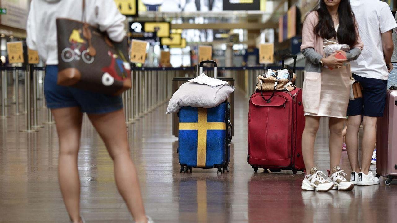 Pasajeros preparándose para el check in en el aeropuerto de Arlanda en Estocolmo, para viajar a Grecia.