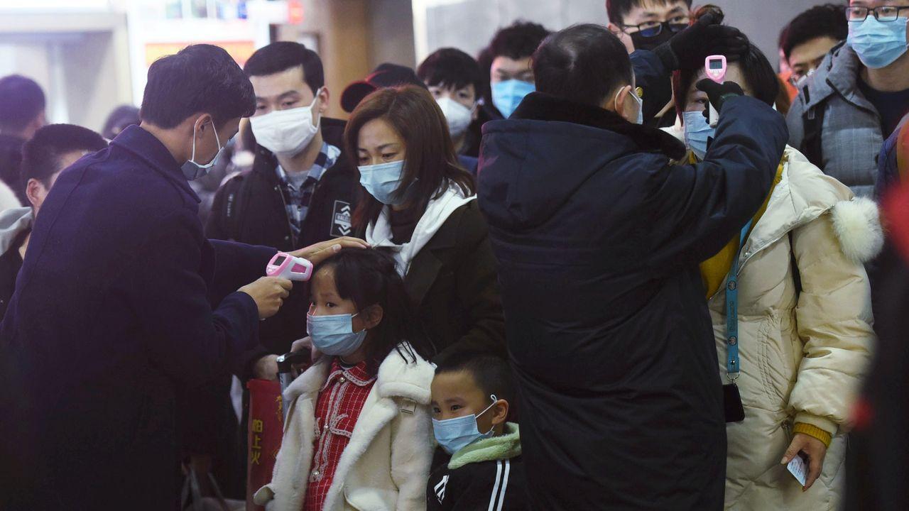 Los miembros del personal verifican la temperatura corporal de los pasajeros que llegan del tren de Wuhan a Hangzhou, en la estación de tren de Hangzhou