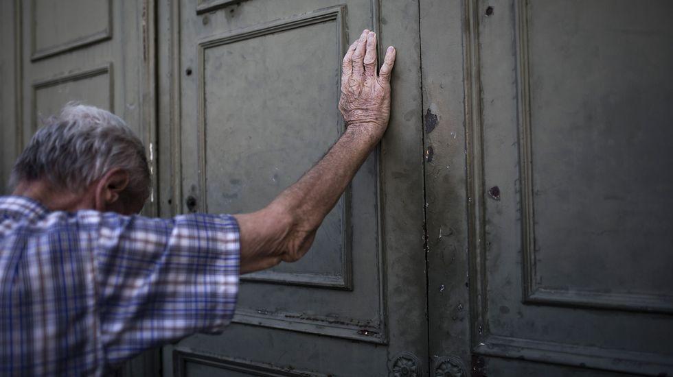 iPhone 7.Un hombre espera en la puerta del Banco Central de Grecia a que abra para sacar dinero.