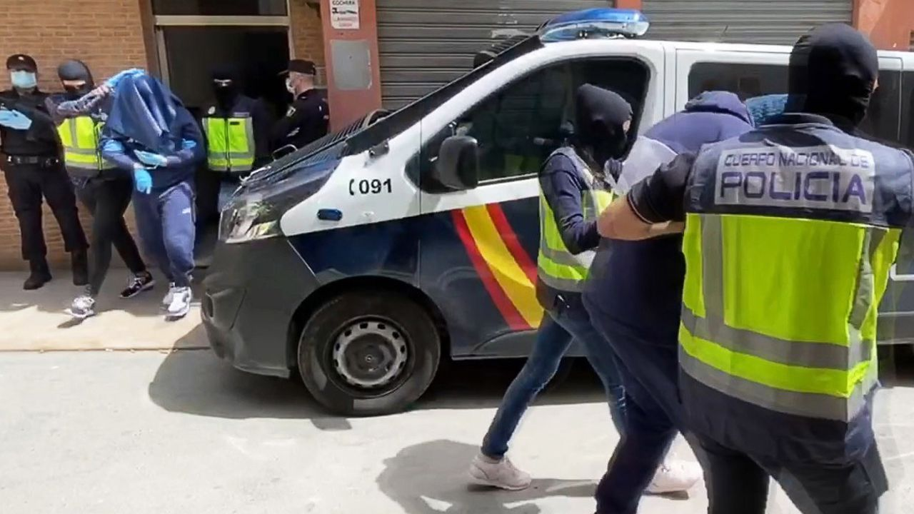 Agentes de policía trasladan a dos de los tres detenidos en la vivieda de Almería donde se escondía el yihadista buscado en Europa