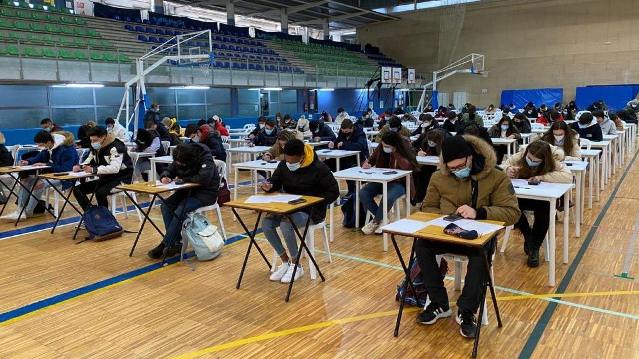 Estudiantes de la Facultad de ADE de Vigo examinándose este lunes, con abrigo y mascarilla, en el pabellón de deportes del campus olívico