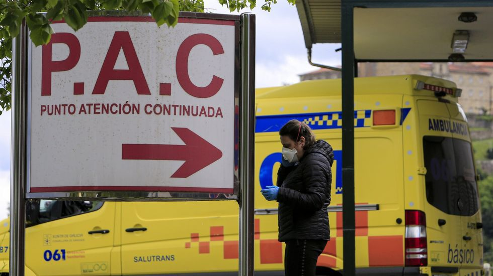 Una mujer con mascarilla frente a la entrada de urgencias del hospital de Monforte