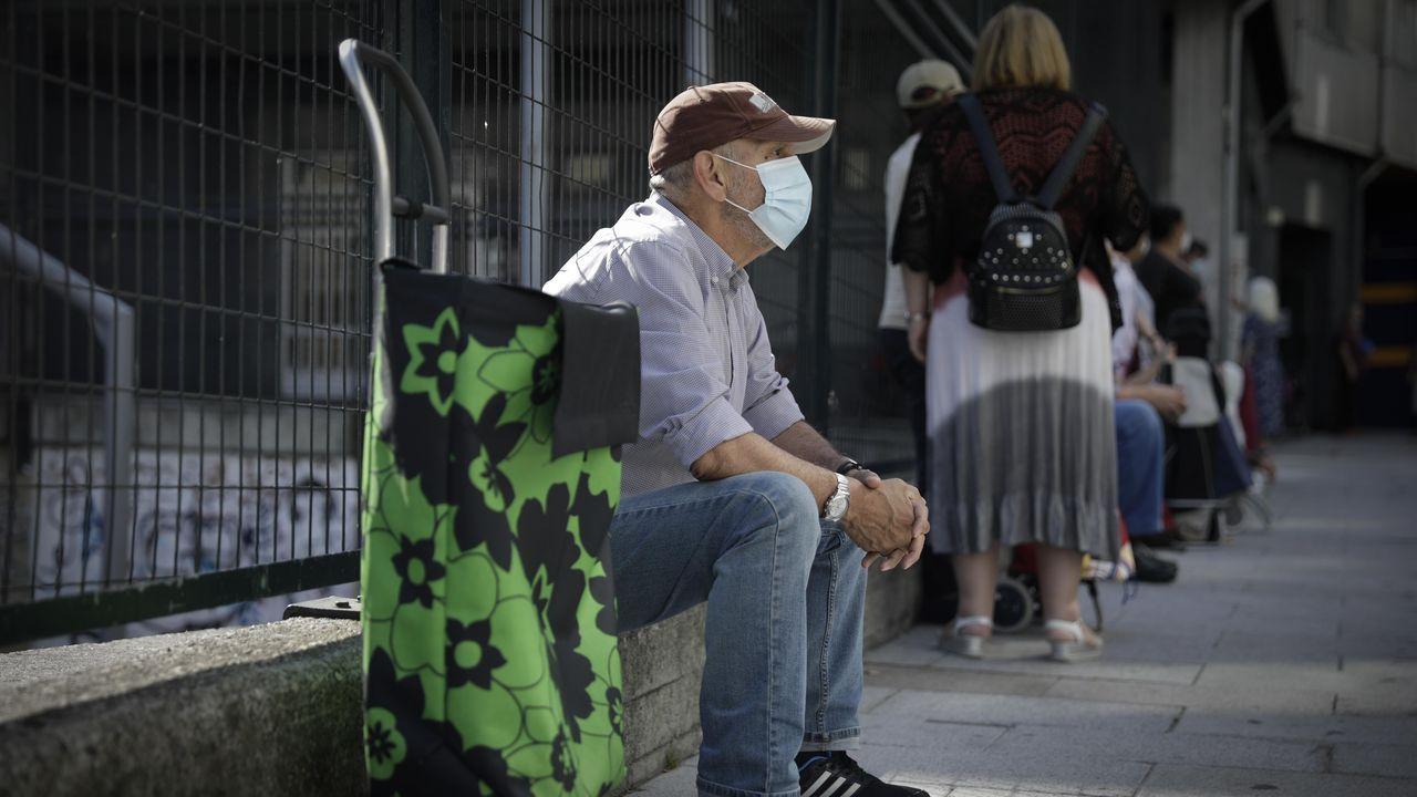 Personas haciendo cola para recibir alimentos ante la asociación Renacer de A Coruña