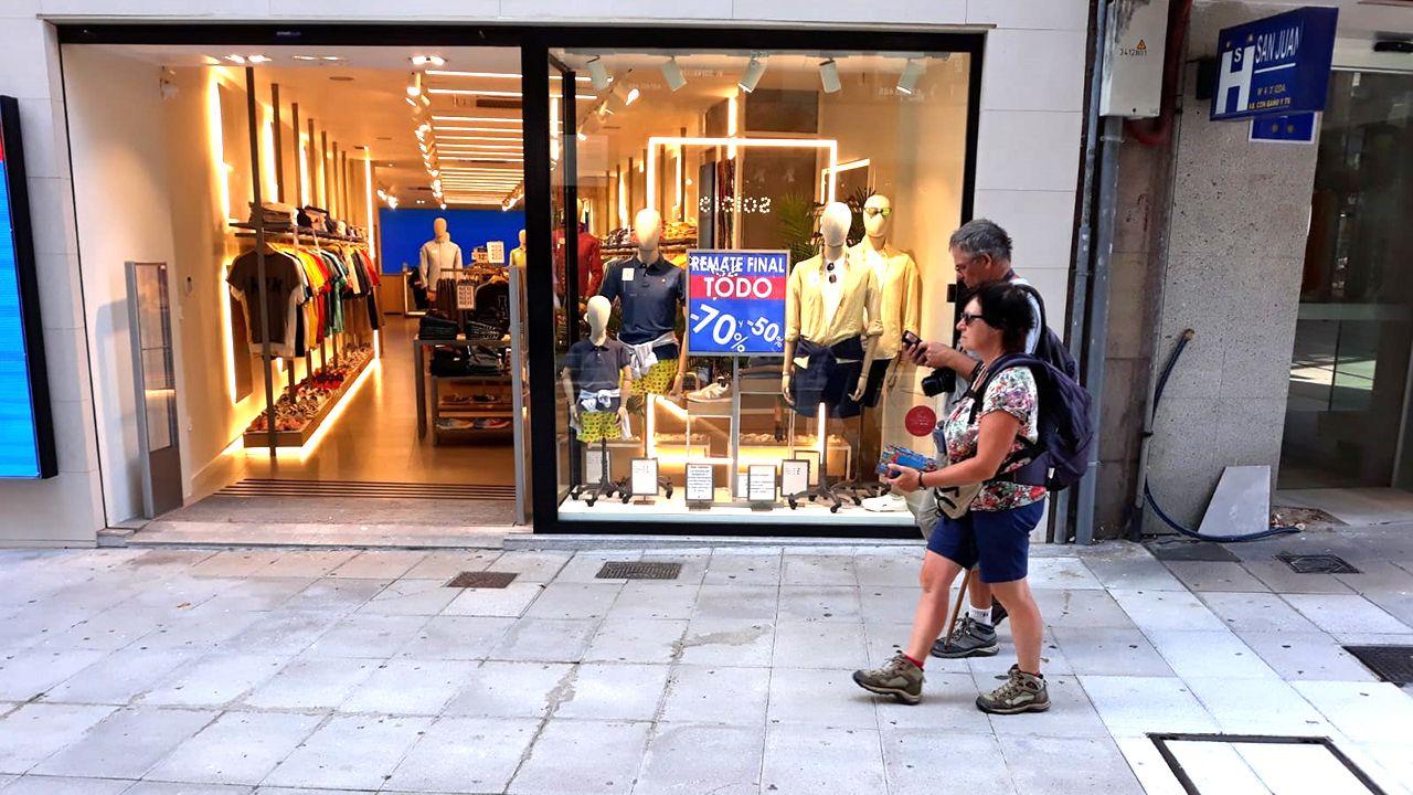 Dos turistas pasan frente a una tienda en rebajas en Oviedo