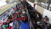 Un grupo de migrantes descansan en las gradas de un estadio de México