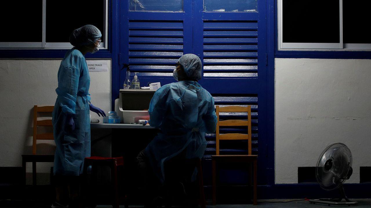 Amor, oración y homenajesa golpe de mascarilla.Doctores de una oenegé de Singapur trabajan en una clínica atendiendo a inmigrantes, uno de los colectivos más castigados por la pandemia