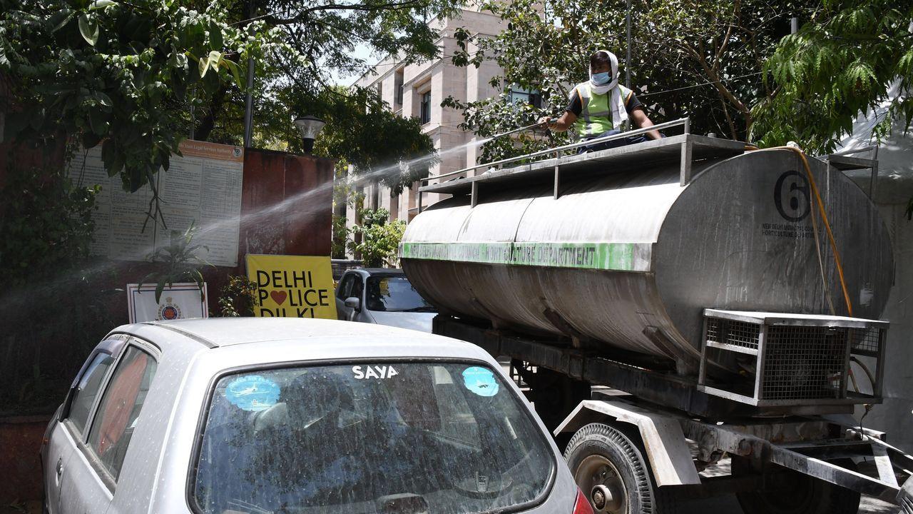En Nueva Dehli los trabajadores municipales desinfectan los alrededores de una comisaría de policía