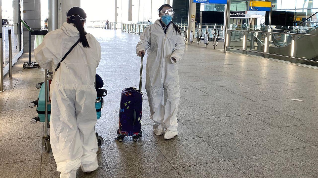 Unas pasajeras ataviadas con monos de protección en el aeropuerto londinense de Heathrow