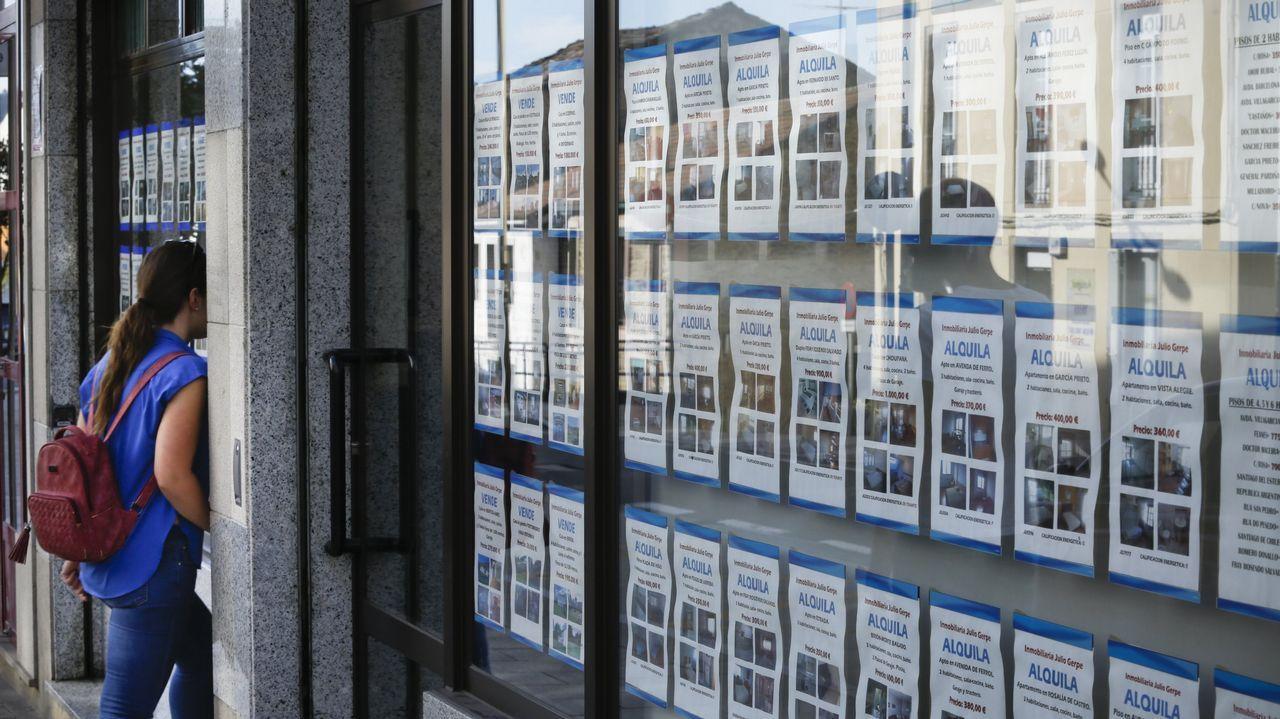 Una mujer observa los anuncios de pisos de alquiler que se exponen en una inmobiliaria de Santiago