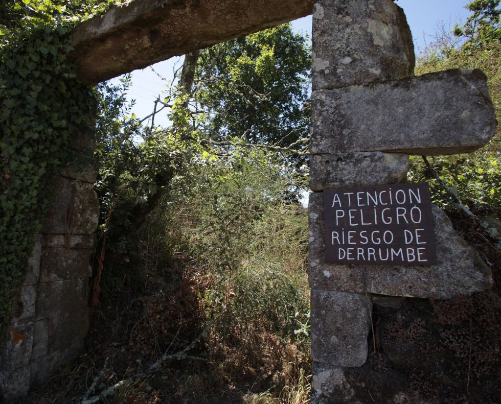 Un cartel advierte del riesgo de derrumbe en una de las entradas al conjunto.