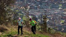 Dos senderistas subiendo al monte Naranco con Oviedo al fondo