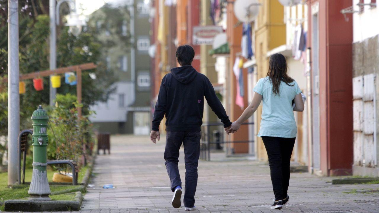 Una pareja camina por el barrio de Recimil