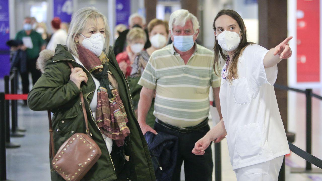 Una sanitaria orienta a dos usuarios para recibir la vacuna contra el covid-19 en el Hospital Lucus Augusti