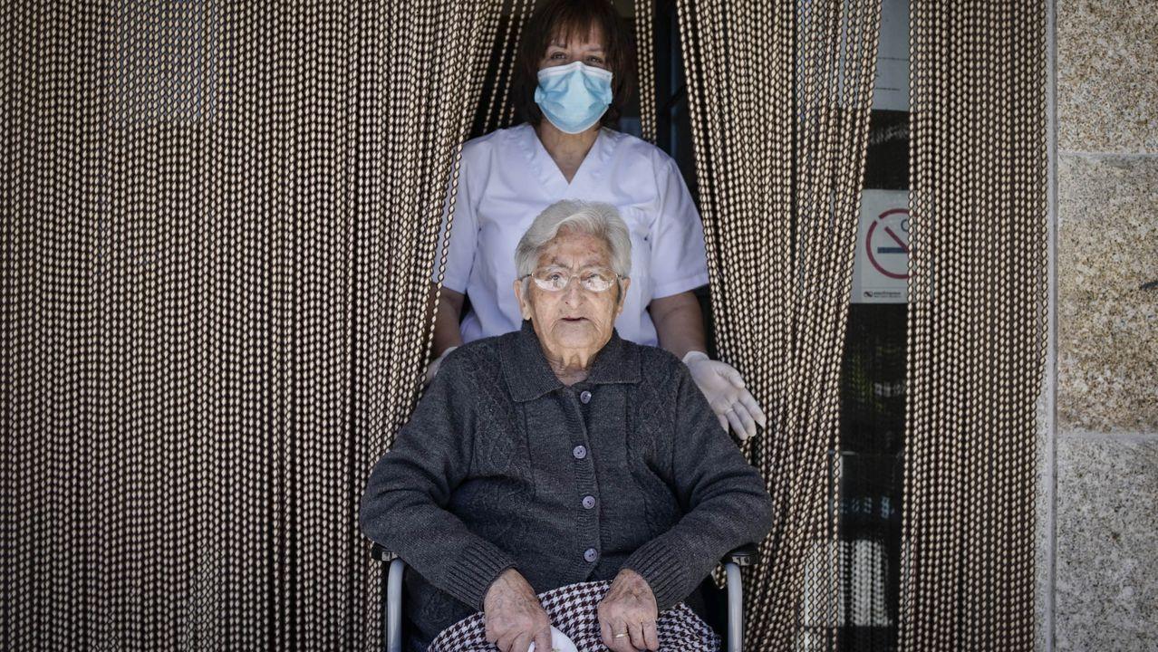 Encarna Enríquez, con su cuidadora Maria, en la puerta de la vivienda comunitaria de Lodoselo