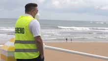 Un empleado de la empresa de Sereno de Gijón controla el acceso a la playa de San Lorenzo, este lunes en Gijón