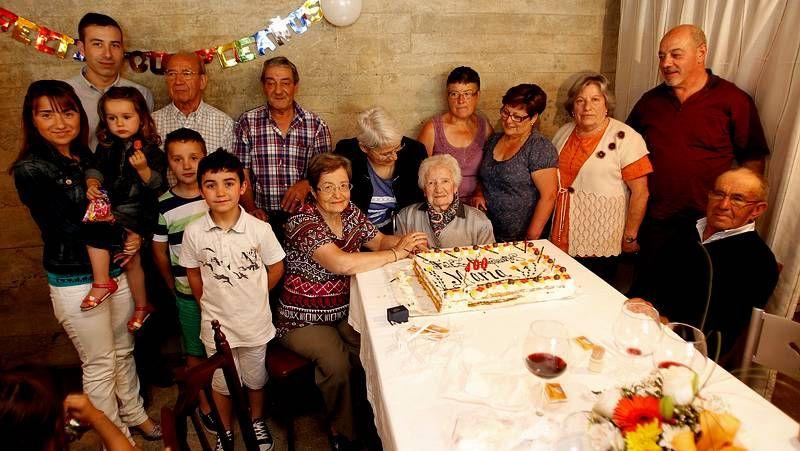 María, sentada en el centro delante de la tarta de cumpleaños