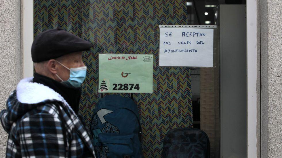 Recogida de la aceituna en el municipio de Quiroga.Un cartel a la entrada de una tienda anuncia que se aceptan los vales municipales