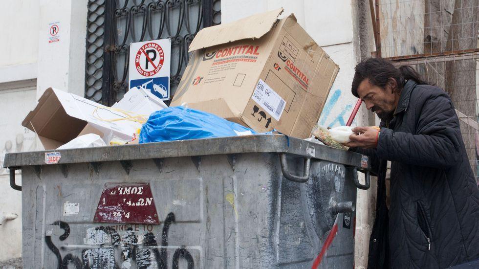 Un hombre busca alimento entre la basura en uno de los barrios más céntricos de Atenas.