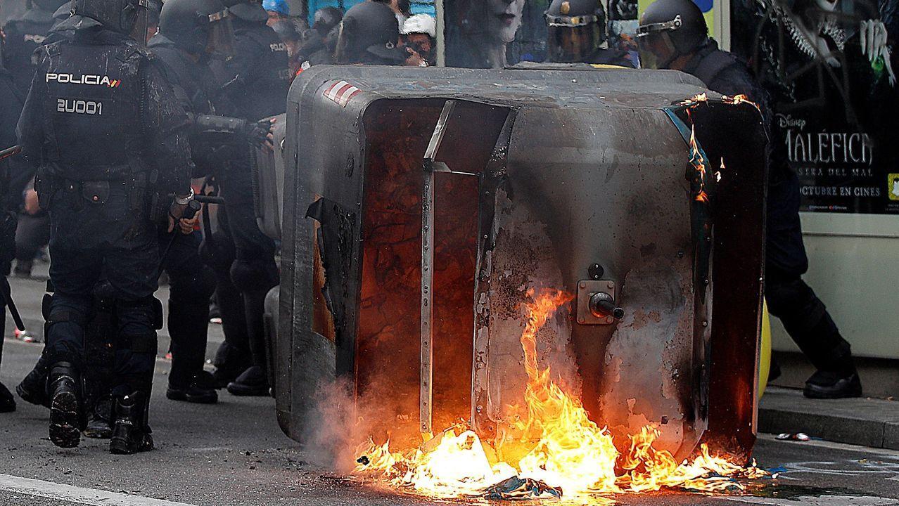 Agentes antidisturbios junto a un contenedor en llamas en Via Laietana