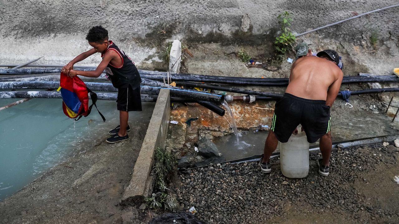 Venezolantos toman agua de una tubería abandonada ante la falta de electricidad y de suministro de agua potable