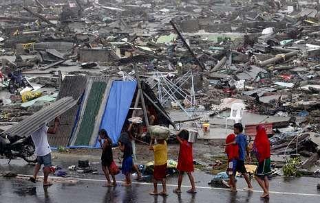 «Rammasun» arrasa Filipinas.Niños filipinos llevan algunos enseres en la ciudad de Tacloban, la más afectada por el tifón «Haiyan»