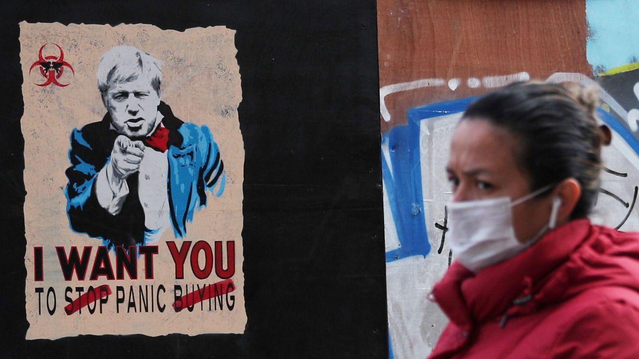Una mujer pasa por un cartel, con un retrato de Boris y el lema «Quiero que dejes de propagar el pánico»