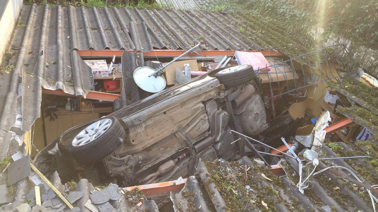 Un coche termina sobre el tejado de un garaje en Betanzos.Accidente en Colloto