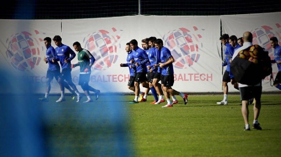 Los jugadores del primer equipo calientan antes de comenzar un entrenamiento