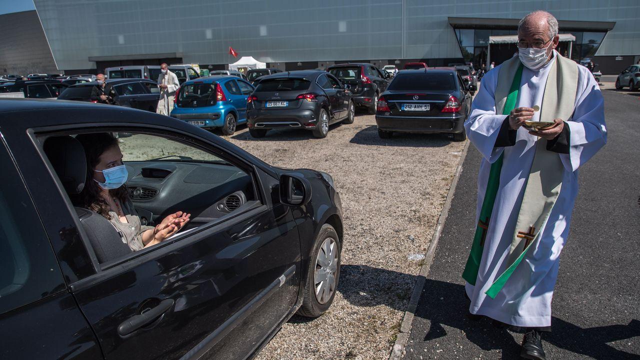 Los sacerdotes llevan la comunión a los fieles a los coches, como si fuese un autocine en la localidad francesa de Chalon-en-Champagne