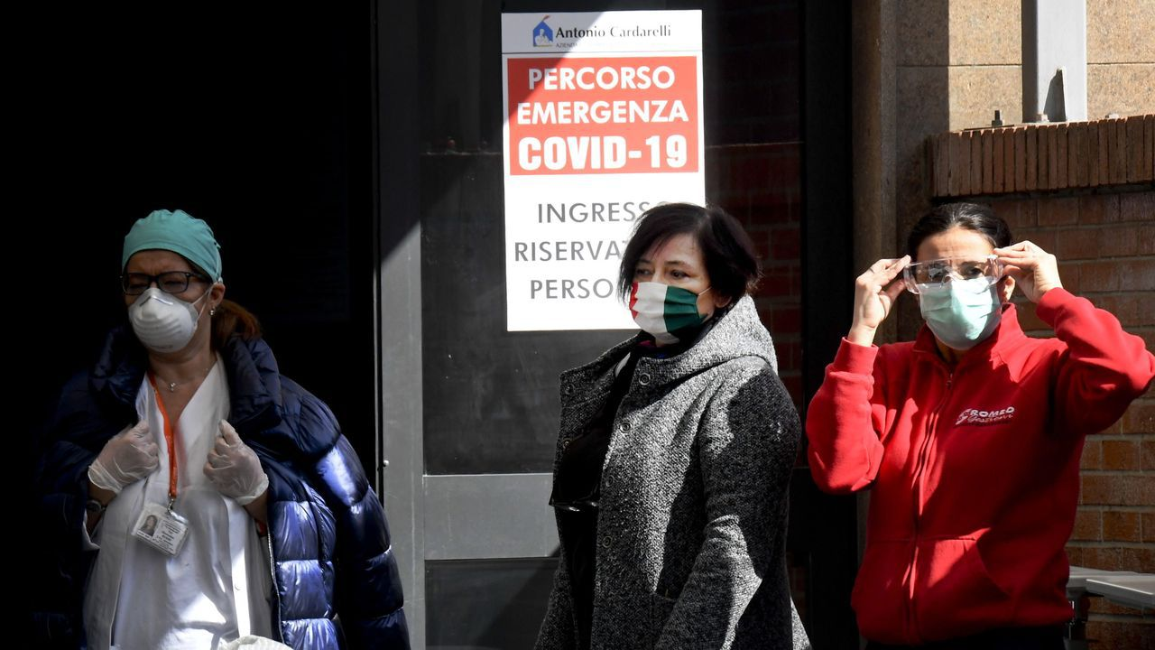 Mujeres con máscaras protectoras, a las puertas de un hospital en Nápoles