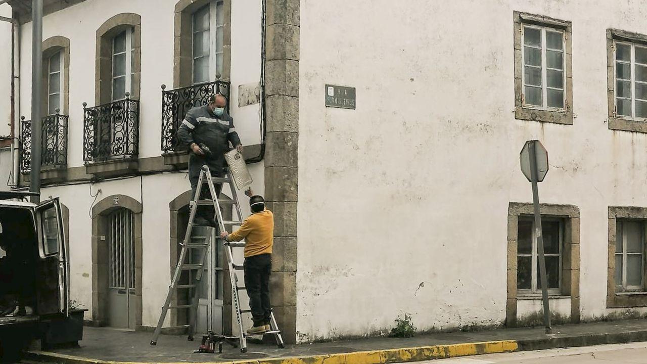 Operarios municipales sustituyendo la placa de José Antonio por la de Xela Arias