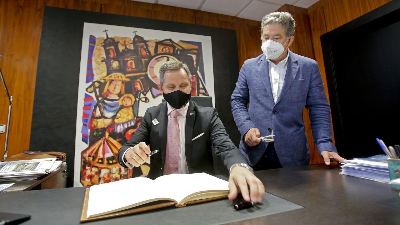 El delegado del Gobierno en Galicia, José Miñones, firma en el libro del Concello de Pontevedra, en presencia del alcalde, Miguel Anxo Fernández Lores
