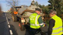 Un guardia civil de Tráfico examina la documentación de un tractor en una carretera gallega