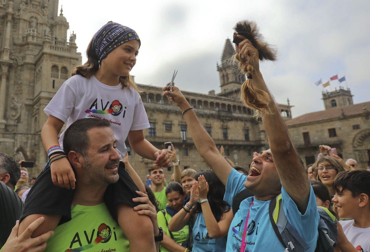 Un padre le corta el pelo a su hija a la llegada a la plaza del Obradoiro de Santiago en la peregrinación contra el cancer infantil
