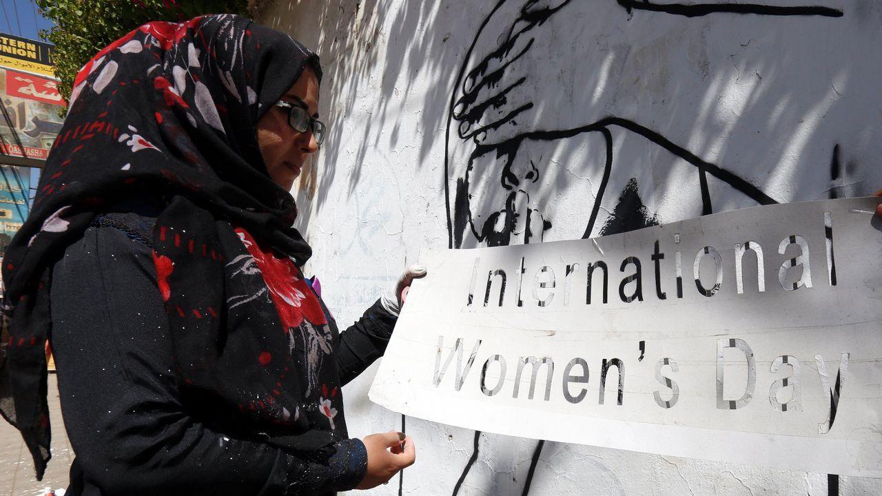 Una mujer pinta una pared en Saná (Yemen)